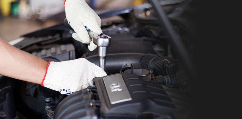 mechanika dokręcający kluczem śrubę wsilniku samochodu